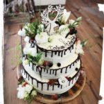 dreistöckige Hochzeitstorte auf einer echten Baumscheibe