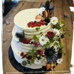 Hochzeitstorte in Streifenoptik mit vielen Blumen