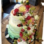 Hochzeitstorte in Streifenoptik mit bunten Blumen